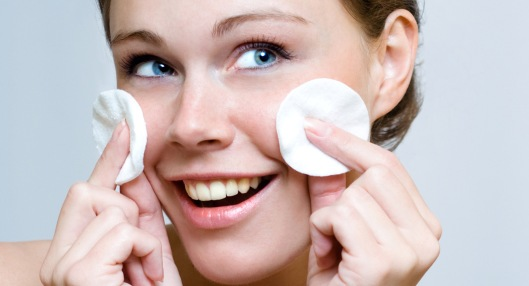 Woman cleaning face by cotton pad